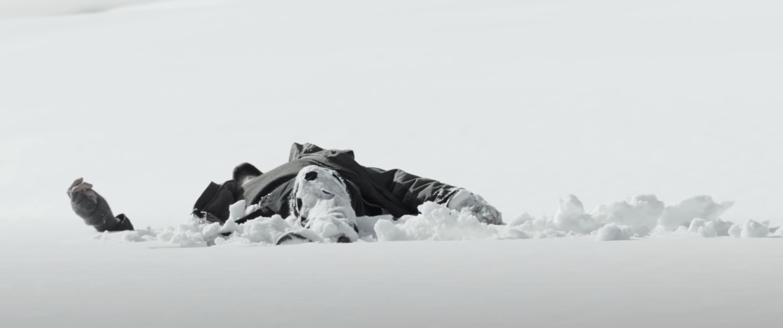 Ein Mann liegt im Schnee.
