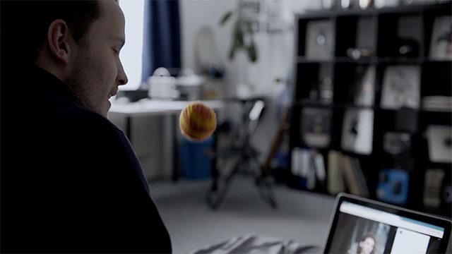 Felix wirft beim Telefonieren einen Ball in die Luft.