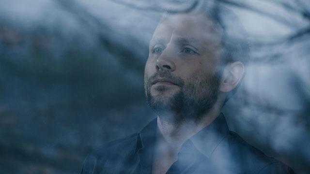 Ein Mann blickt durch eine Fensterscheibe.